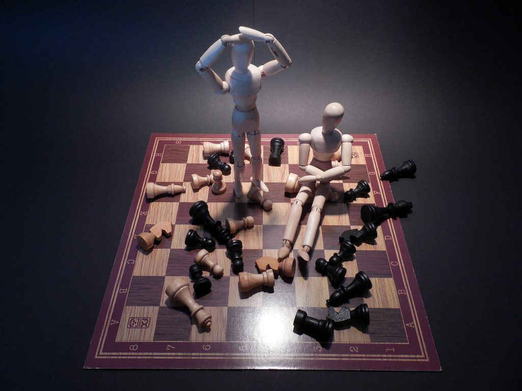 Zwei Gliederpuppen stehen bzw. sitzen auf einem Schachbrett mit umgeworfenen Spielfiguren