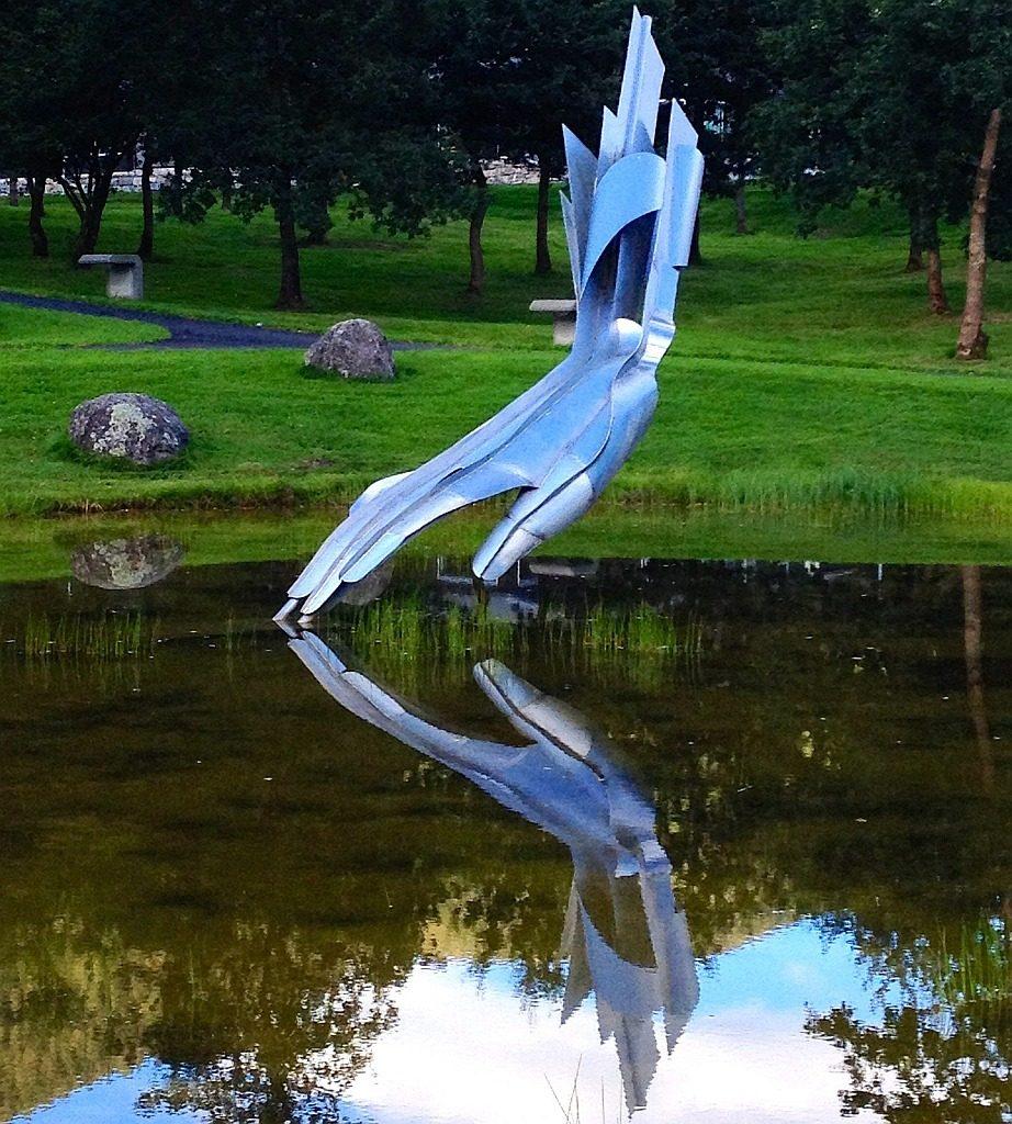 Die Skulptur einer stilisierten blauen Hand über einem Teich, die mit den Fingenspitzen ihr eigenes Spiegelbild im Wasser berührt