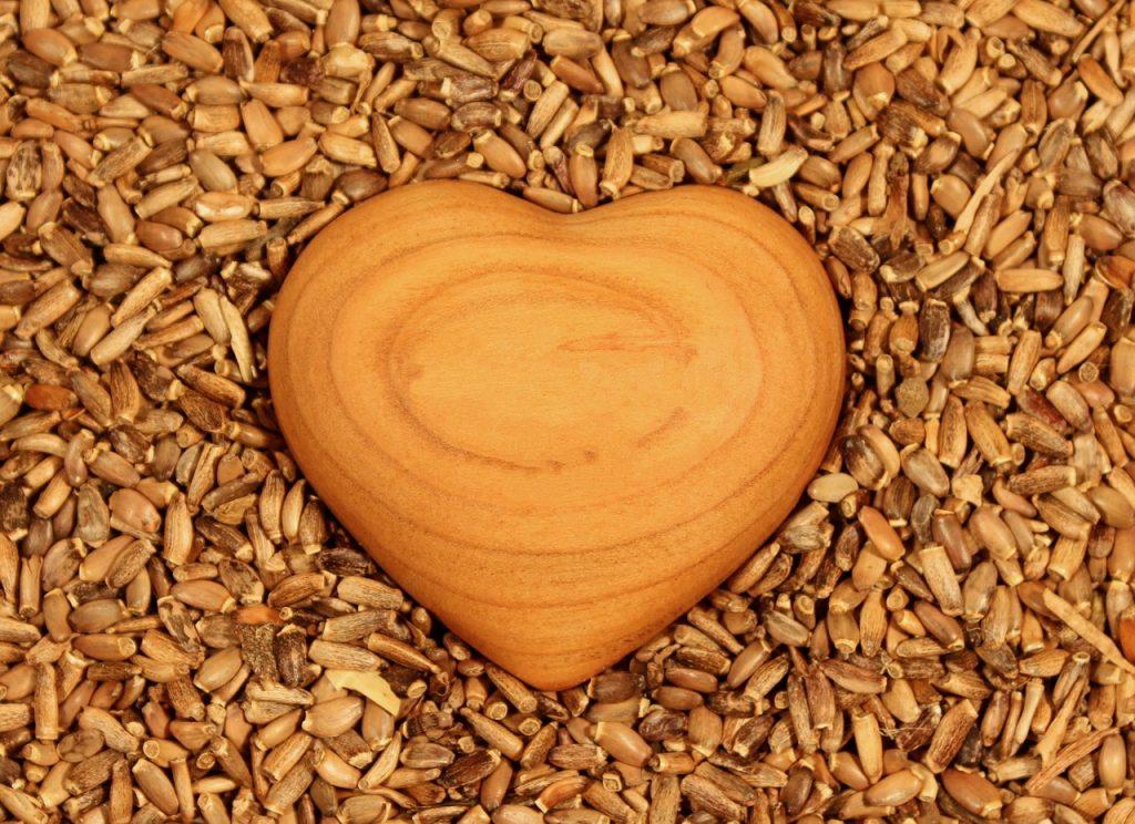 Ein Herz aus Holz liegt inmitten von Körnern