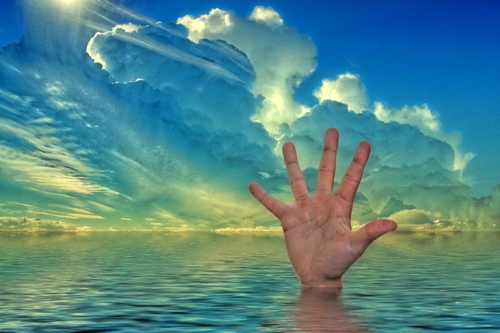 Eine Hilfe suchende Hand streckt sich aus dem Wasser