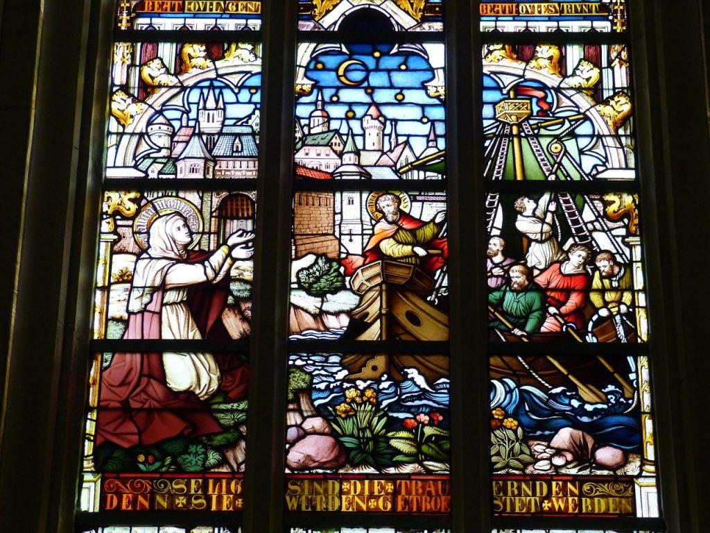 """Kirchenfenster mit der Unterschrift: """"Selig sind die Trauernden"""" und einem Bild von einer Frau, die am Ufer zu einem mit Männern besetzten Boot hinübergrüßt"""