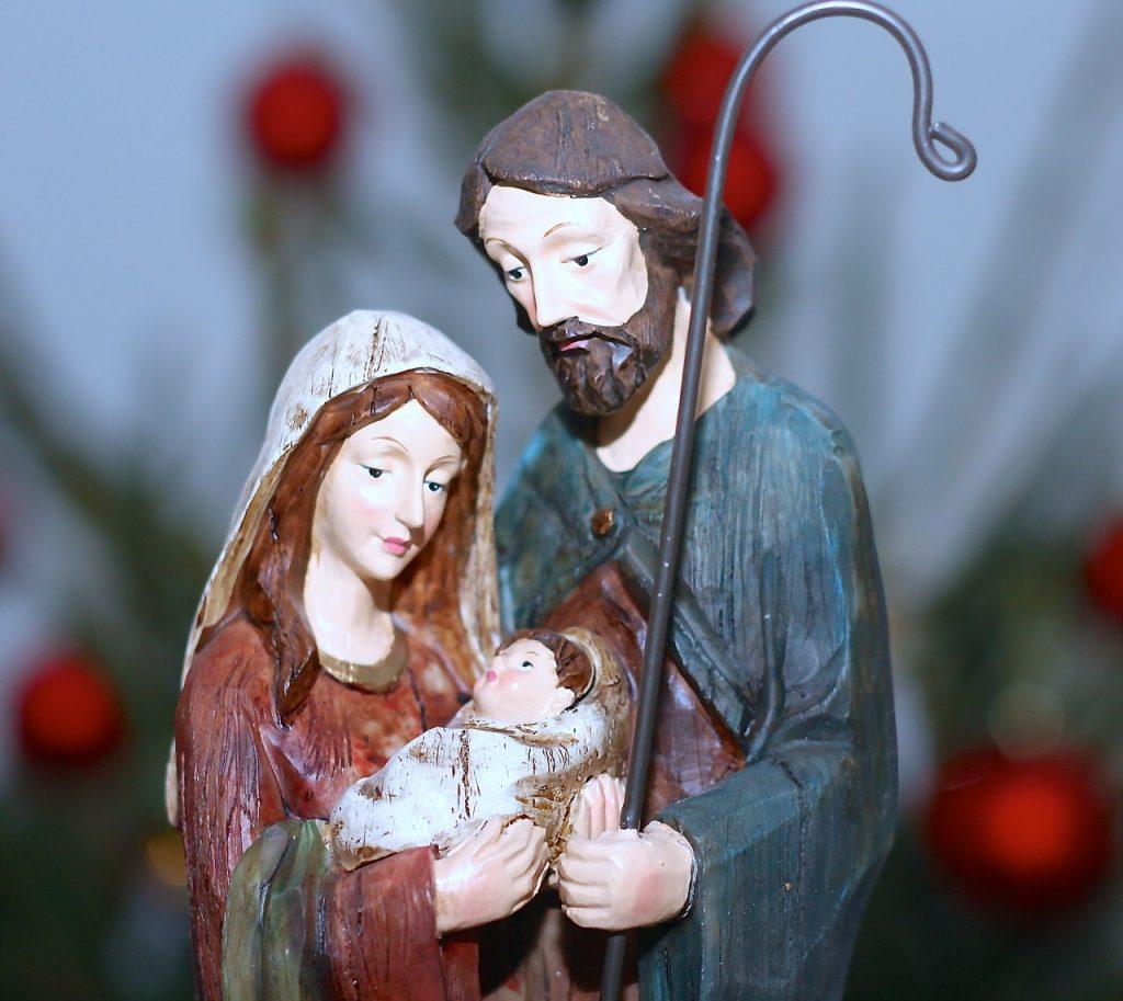 Josef und Maria stehen eng beieinander und halten gemeinsam das Jesuskind umfangen