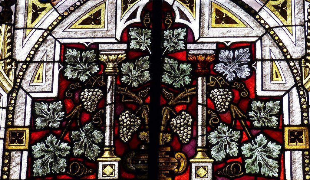Ein Kirchenfenster mit dem Symbol des Weinstocks, an dem viele Reben mit Trauben hängen