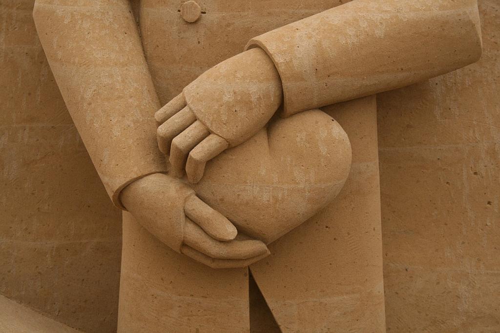 Eine Sandskulptur mit zwei Händen, die ein Herz beschützend festhalten