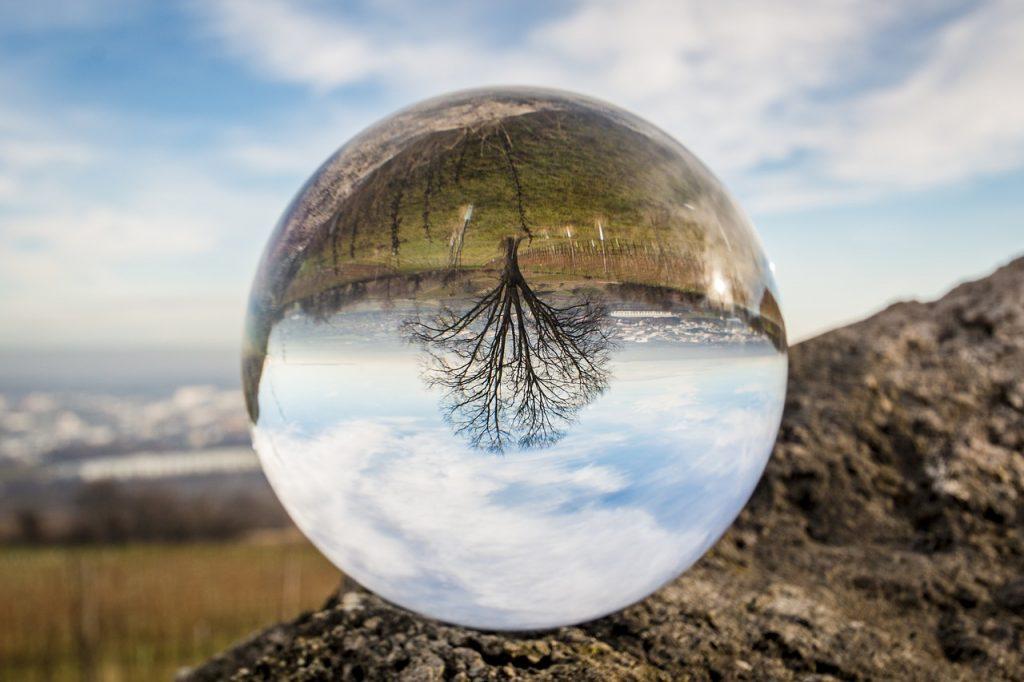 Eine Glaskugel mit dem umgekehrten Bild einer Landschaft mit Baum