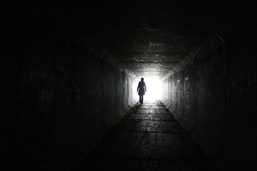 Ein Mensch steht hinten in einem dunklen Tunnel - am Ende leuchtet es hell