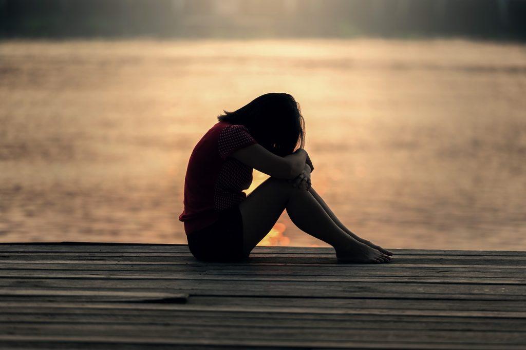 Die Silhouette einer Frau, die traurig am Strand sitzt
