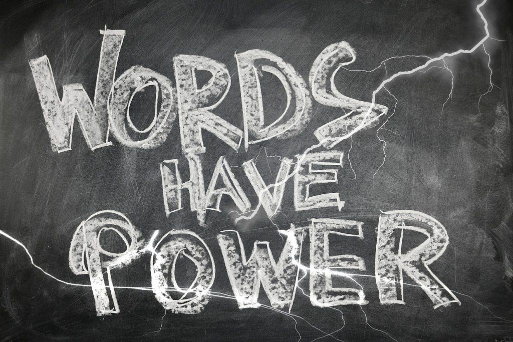 """Schrift mit weißer Kreide auf einer Schiefertafel: """"Words have power"""""""