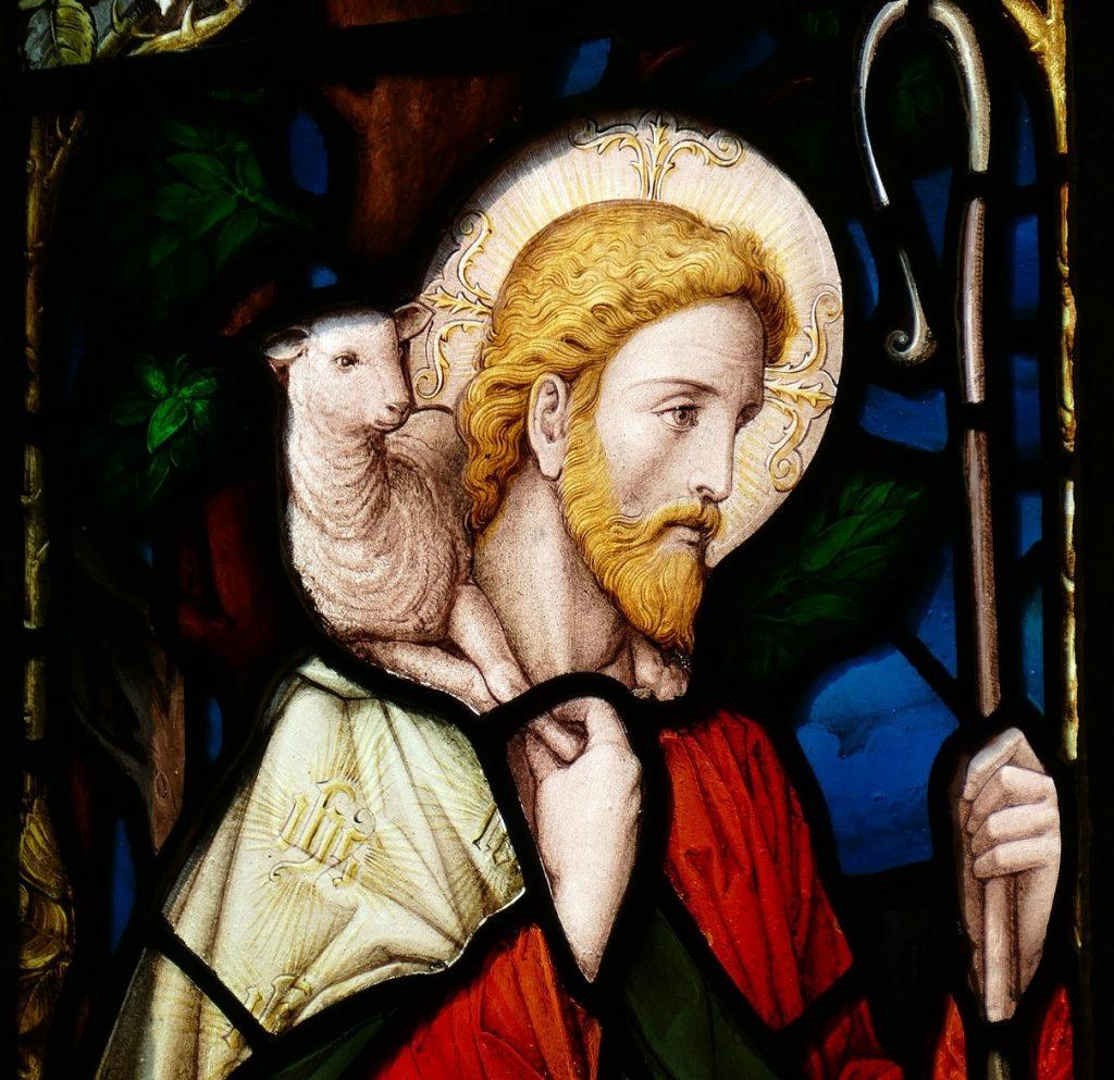 Kirchenfenster mit Jesus als dem Guten Hirten mit Schaf auf der Schulter und Hirtenstab in der Hand