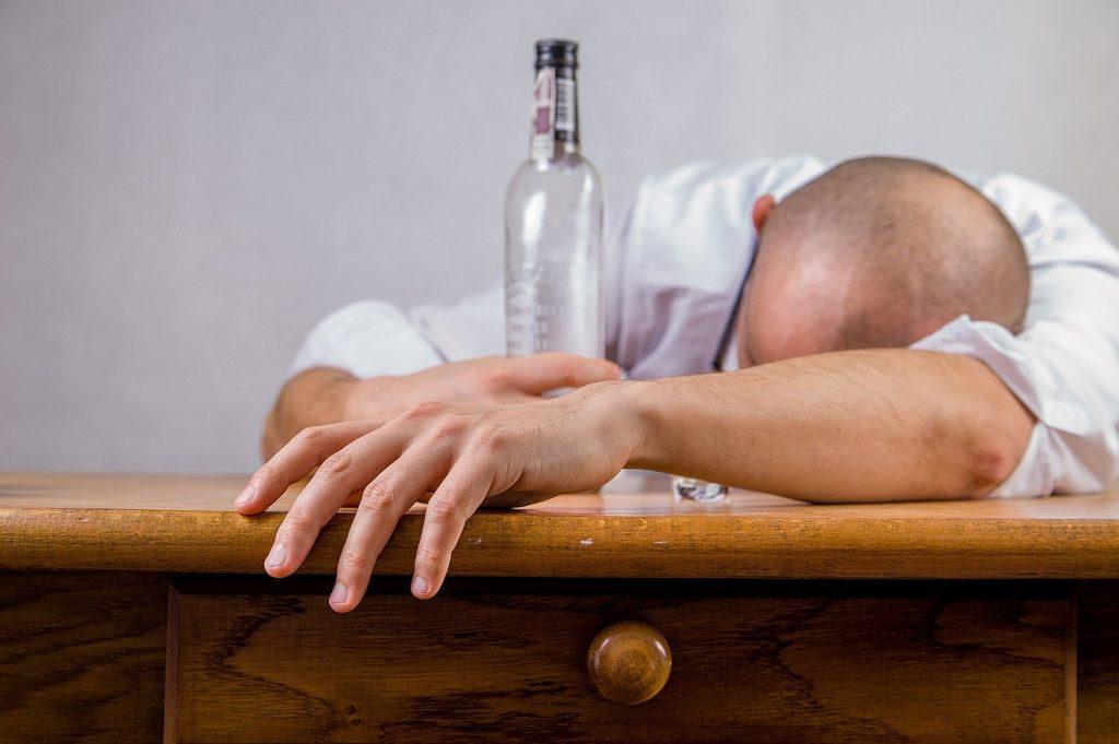 Überwindung der Alkoholkrankheit: Ein Mann, der sich betrunken hat, liegt mit dem Kopf auf einem Tisch, die Schnapsflasche noch in der Hand