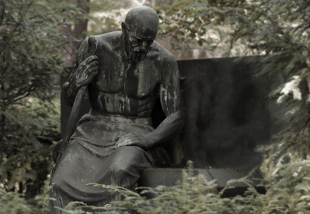 Statue eines Mannes, der allein auf dem Friedhof an einem Grab sitzt und trauert