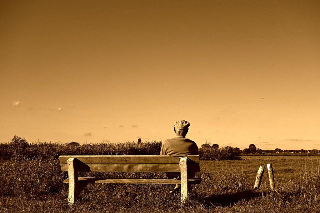 """""""Er starb alt und satt an Tagen"""": Ein alter Mann sitzt auf einer Bank und schaut in die Weite einer ebenen Landschaft"""