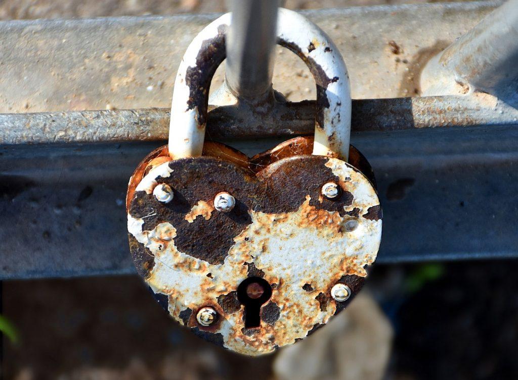 Korrekt in der Arbeit, treu in der Ehe: Ein herzförmiges Vorhängeschloss an einer Brücke, verrostet, aber weiterhin geschlossen