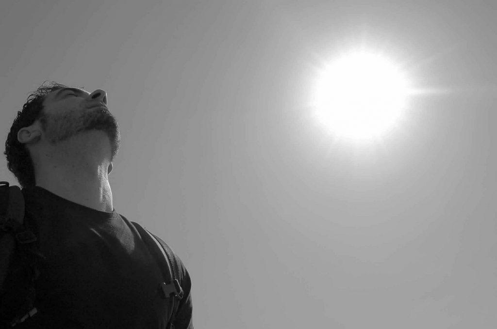 Beten ist das Atmen der Seele: Ein Mann mit dem Kopf im Nacken und geweiteter Brust wendet sein Gesicht der Sonne zu