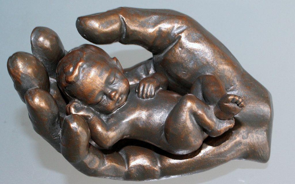 Jesus will uns nicht als Waisen zurücklassen: Bronze-Skulptur einer Hand, in der ein kleines Kind geborgen schlafen kann