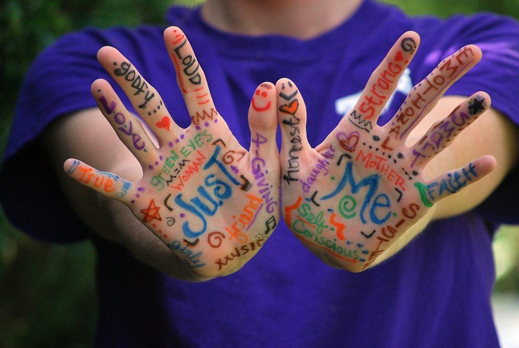 """""""Ich habe dich eingezeichnet in meine Hände"""": Jemand hält seine bemalten Handflächen dem Betrachter entgegen, darauf stehen Worte wie """"Just"""" + """"Me"""" und viele ermutigende Stichworte"""