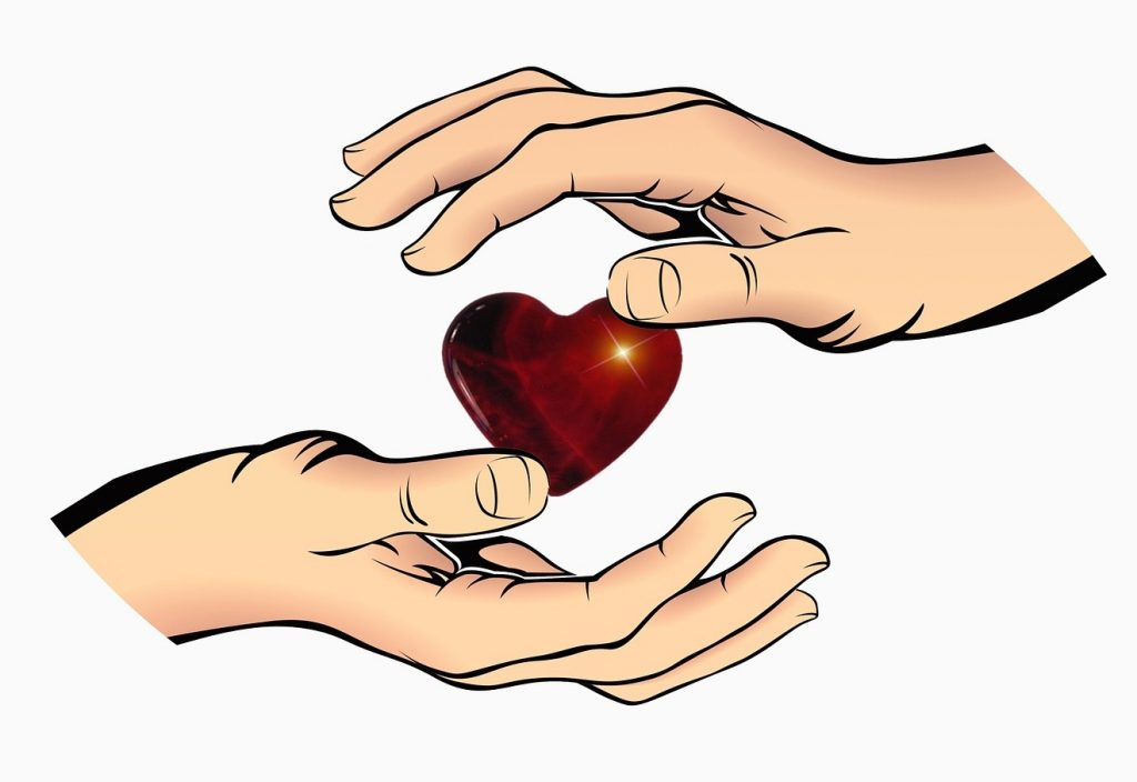 """""""Von allen Seiten umgibst du mich"""": Zwei Hände beschützen ein Herz von unten und von oben"""