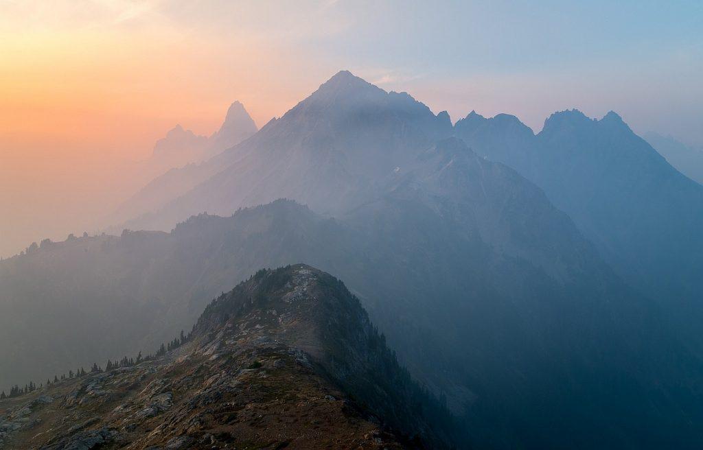 Ein Leben in stiller, ruhiger Beständigkeit: Blick in hintereinander liegende eindrucksvolle Berge im Dunst und Abendlicht