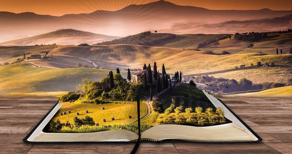 Gott stellt uns auf den weiten Raum der Liebe: In einer weiten hügeligen Landschaft führt eine Straße hin zu schön beleuchteten Bergen, im Vordergrund liegt ein Buch mit einer Feld- und Waldlandschaft