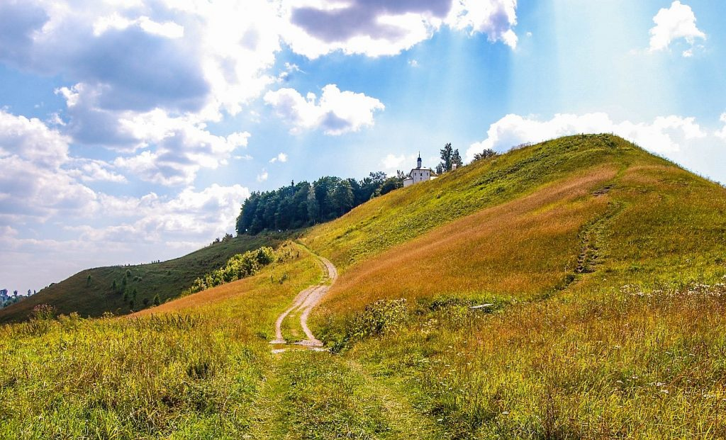 """""""Dem HERRN befehlen - er wird's machen"""": Wege, die auf einen Hügel führen, auf dem eine kleine Kapelle steht, darüber ein sommerlich bewölkter strahlender Himmel"""