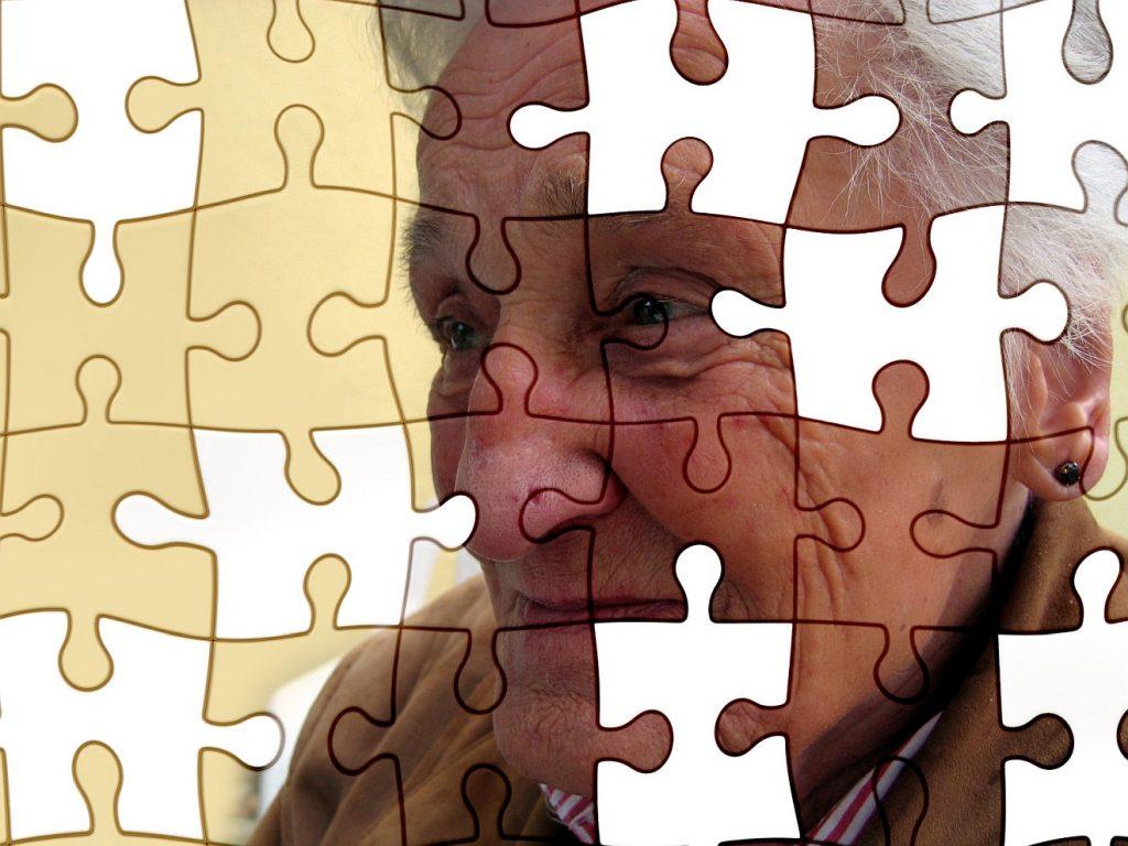 In der Demenz behält der Mensch seine Würde: Ein Bild einer alten Frau, als Puzzle dargestellt, in dem einige Teile fehlen