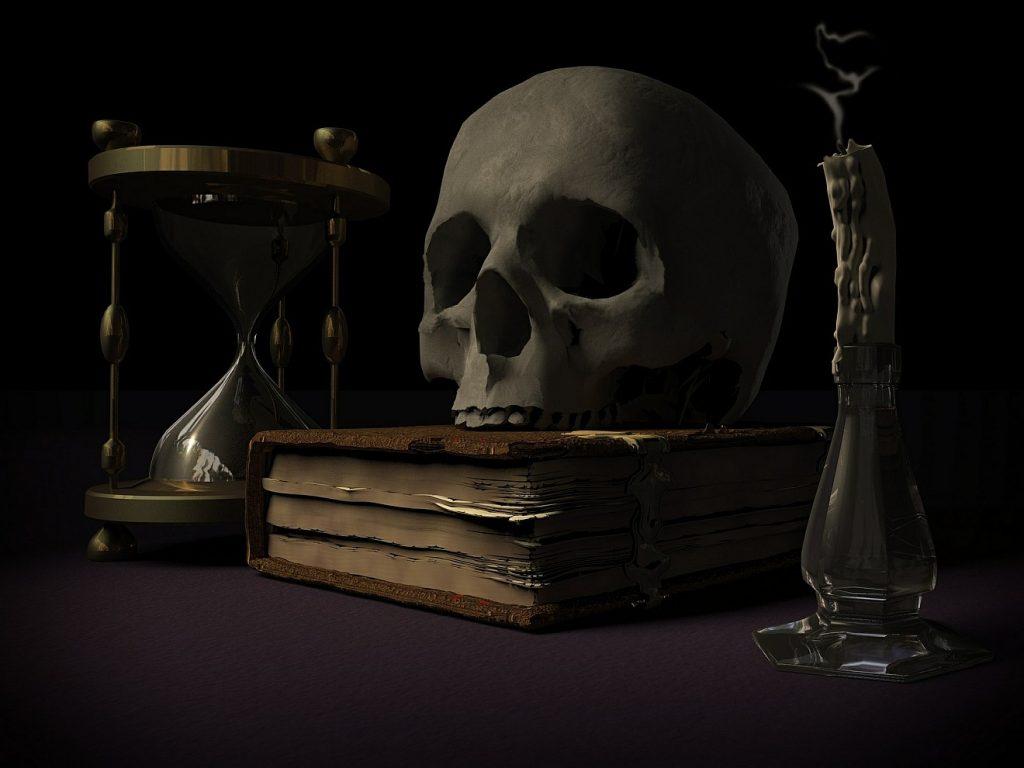 """""""Die Toten wissen nichts"""": Ein Totenschädel auf einem Buch neben Sanduhr und gelöschter Kerze"""
