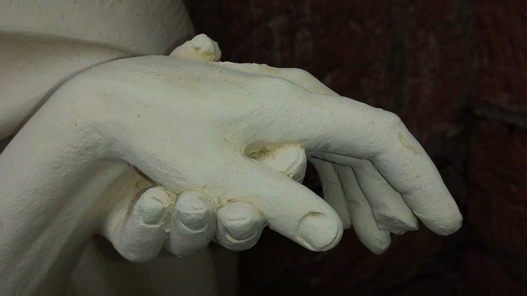 """""""Dient einander als Haushalter der Gnade Gottes"""": Die Hand einer Statue hält eine andere"""