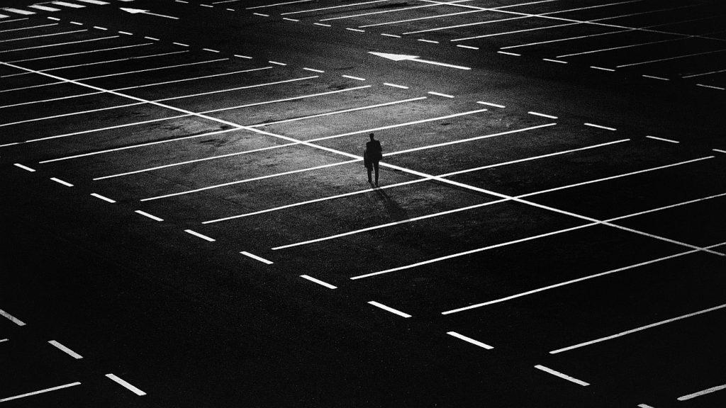Doch nicht ganz einsam: Ein einzelner Mann auf einem riesigen dunklen Parkplatz