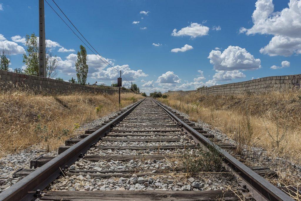 """""""Wer beharrt bis ans Ende, der wird selig"""": Eisenbahnschienen, die schnurgerade zu einem Horizont unter blauem Himmel führen"""