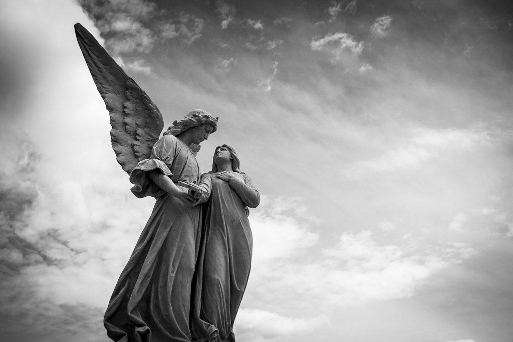 Von Engeln hinüber in den Himmel getragen: Die Statue eines Engels und eines Mädchens, das er begleitet, vor einem bewölkten, aber eher hellen Himmel