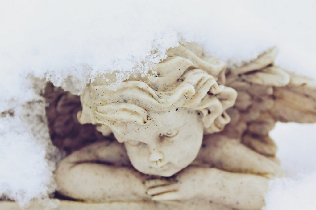 Kein Kindergrab für ihre Tochter: die Figur eines kleinen Engels mit dem Kopf auf den verschränkten Armen, von Schnee bedeckt