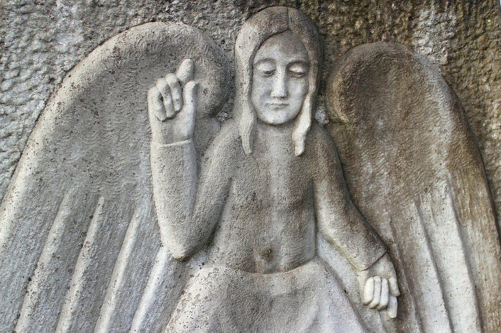 Ein schlichter Engel, als Stein-Relief mit Flügeln abgebildet, zeigt nach oben