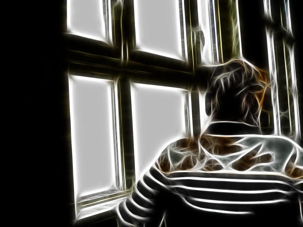Erfülltes Leben in der Demenz? Eine alte Frau im Rollstuhl von hinten vor einem Fenster mit Fensterkreuz
