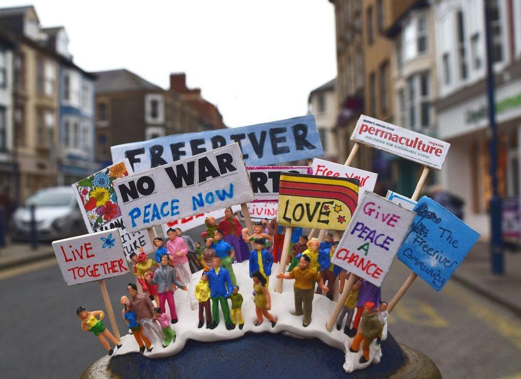 Mächtig ist, wer sich einsetzt für Frieden, Umwelt, Liebe. Das Bild zeigt eine Torte mit entsprechenden Protestplakaten auf der Straße