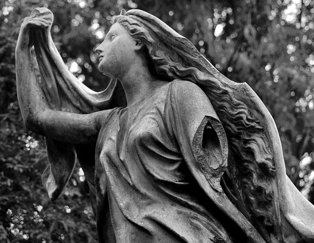 Ein kaltes, gebrochenes Halleluja: Ein Friedhofsengel, der den rechten Arm erhebt und dessen linken Arm abgebrochen ist