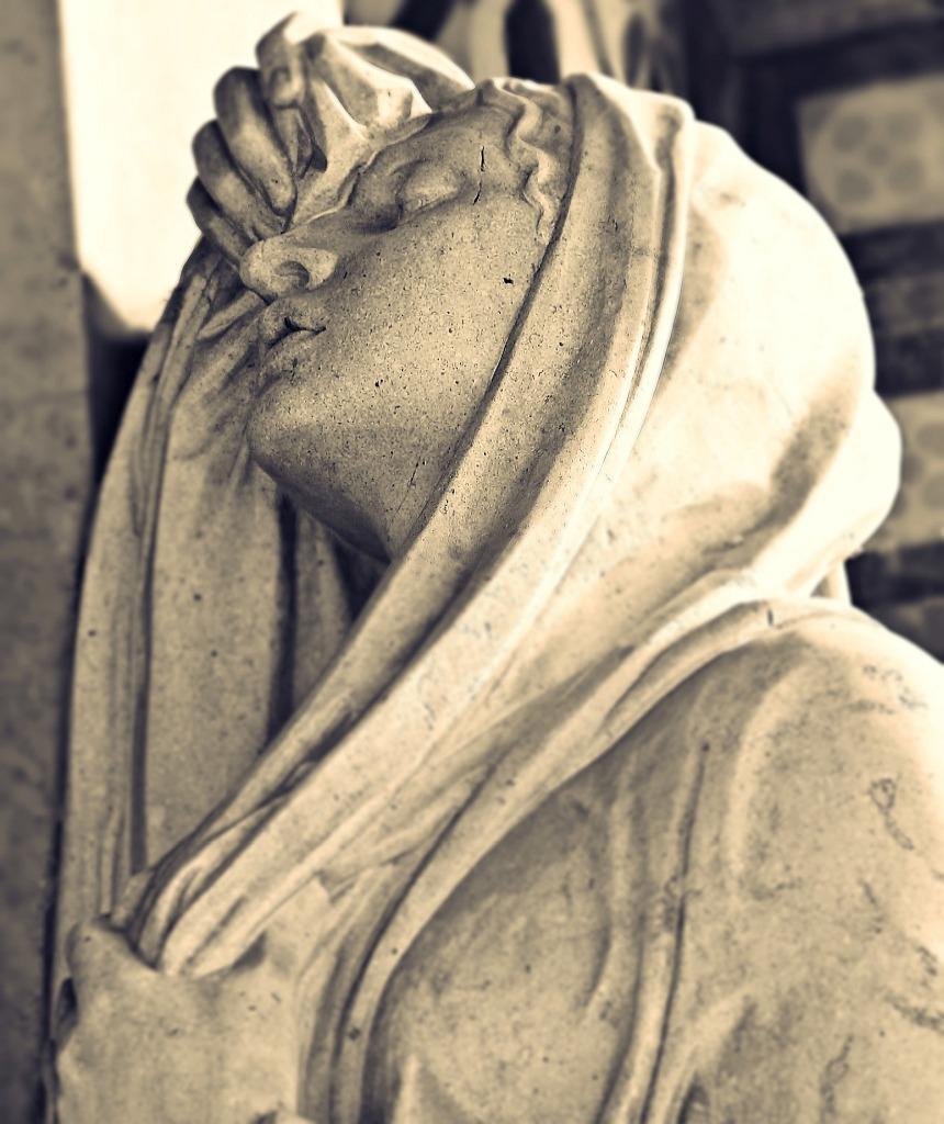 Leben und Sterben in Würde: Skulptur einer Frau mit einem Kopftuch, die ihre Augen geschlossen hat und Schmerz zu erleiden scheint
