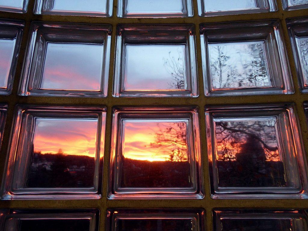 Bausteine für das Glück im HImmel: Glasbausteine mit Durchblick zu einer Sonnenuntergangsstimmung am Himmel