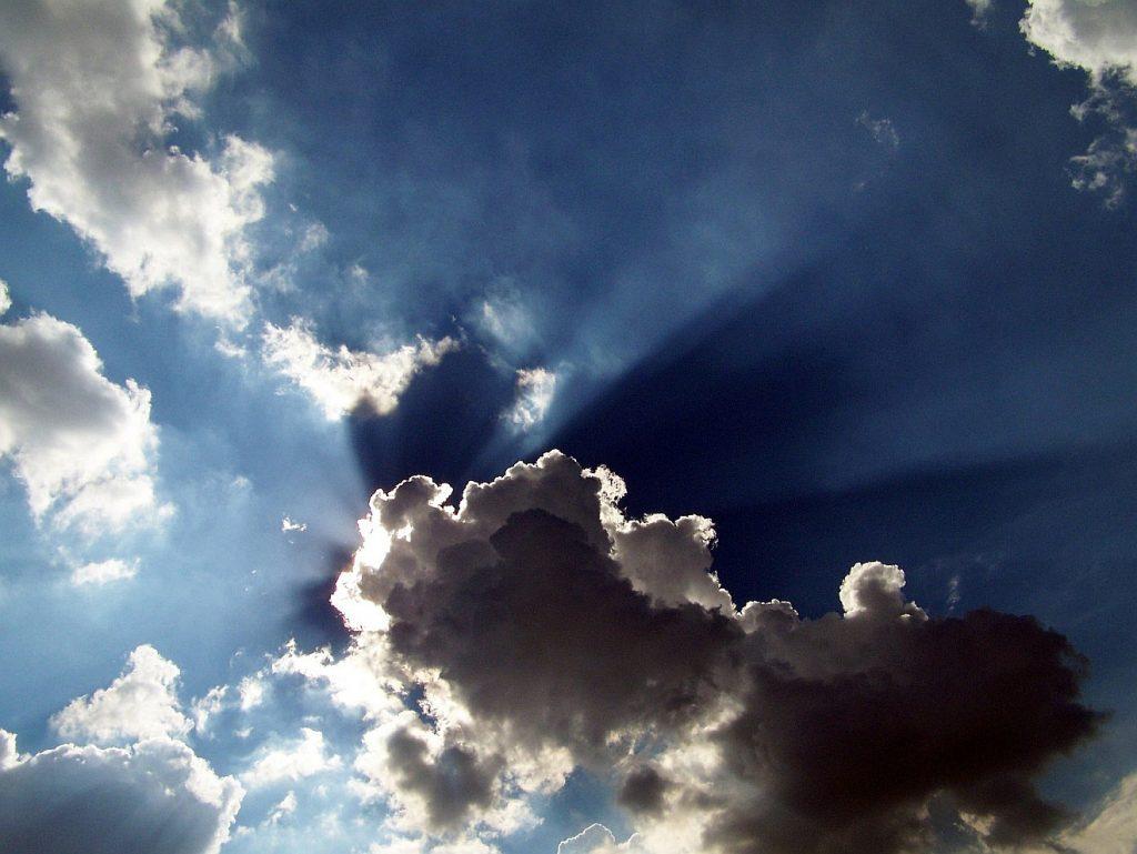 Hinter hellen und dunklen Wolken brechen Sonnenstrahlen hervor