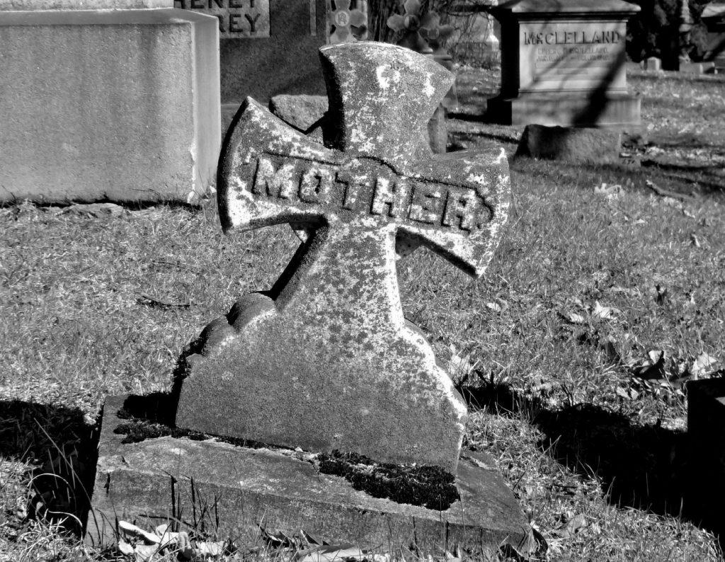 """Auf Gott geworfen von Mutterleib an: Schiefes altes Grabkreuz mit dem Schriftzug """"Mother"""" = """"Mutter"""""""