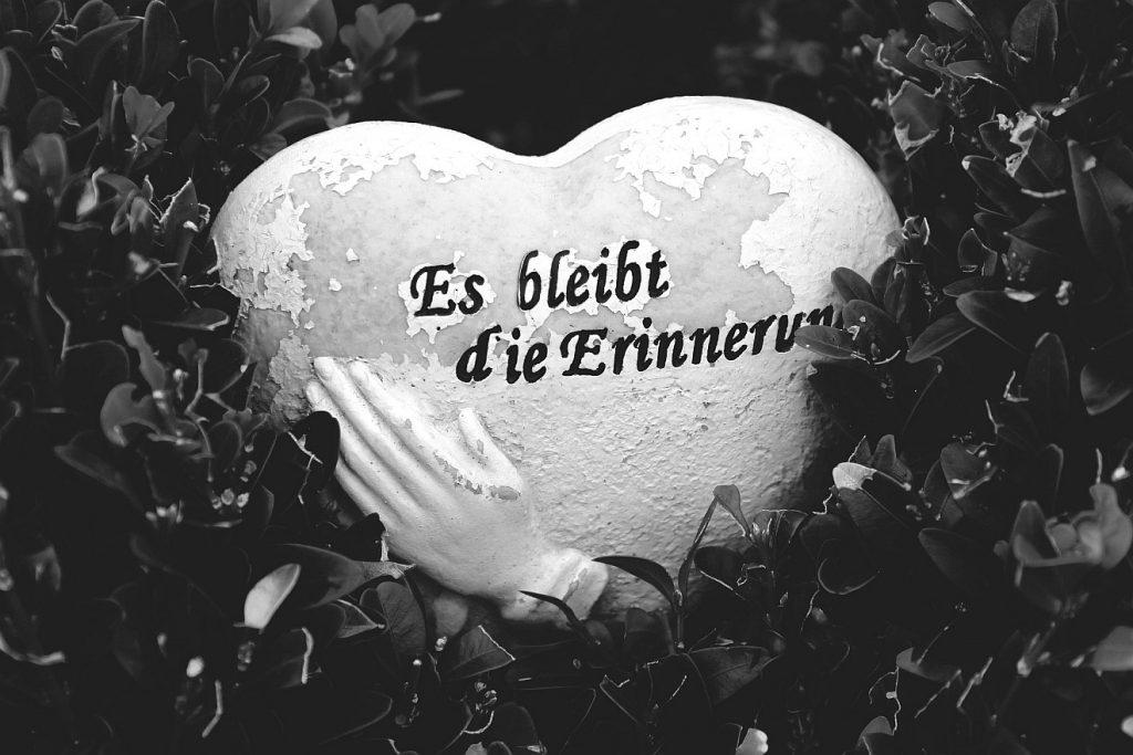 """Gottes Liebe beruhigt die Unruhe des Herzens: Ein Herz als Grabstein mit einer betenden Hand und der Inschrift: """"Es bleibt die Erinnerung"""""""