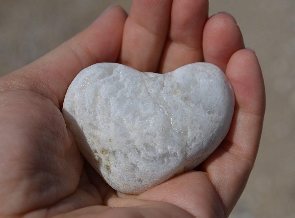 Mehr geben als empfangen: Ein herzförmiger Stein, gehalten von zwei Händen