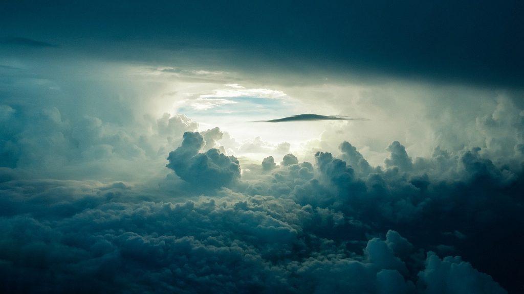 Von Gott in den Himmel abgeholt: Wolkenformation, über den Wolken fotografiert, in der Ferne blauer Himmel wie ein Tor hinter einer geheimnisvollen Wolkenlandschaft
