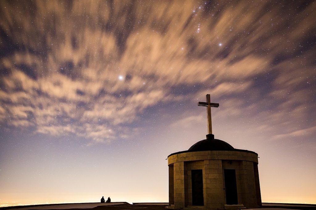 """""""Der HERR nimmt mich auf"""": Eine Kirche, daneben kleine Menschen, darüber ein Abendhimmel mit hellen Wölkchen und vielen Sternen"""