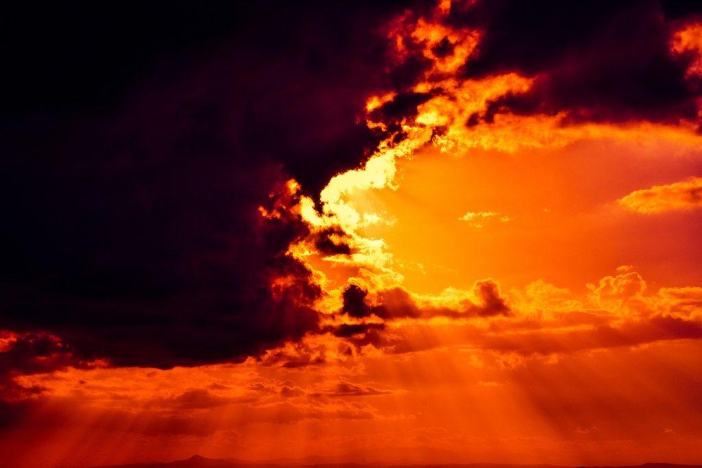 Visionen vom Licht des Himmels: Die Sonne, die hinter schwarzen Wolken hervorbricht, erzeugt ein wunderbares rotgelbes Himmelsfeuer