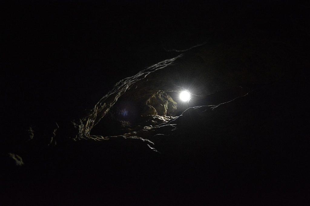 In einer tiefschwarzen Höhle leuchtet in der Entfernung ein Licht