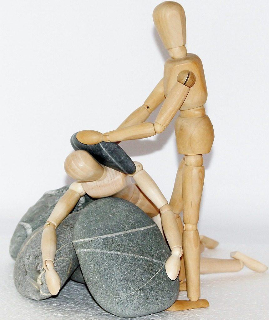 Tief gebeugt und voll Vertrauen: eine Holzfigur, von Steinen umschlossen, vertraut sich einer stehenden Holzfigur an, die ihr einen Stein auf die Schulter legt - mit dem Ziel der Heilung