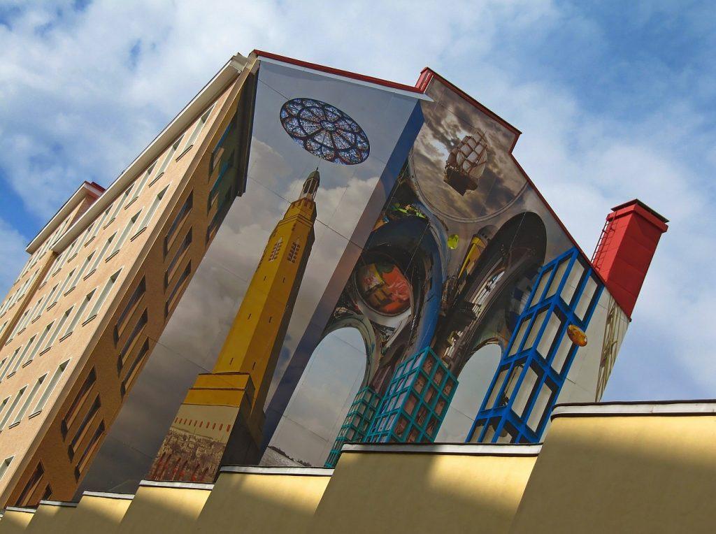 Im Guten wohnen: Ein großes schräg fotografiertes Gebäude mit eindrucksvollen Wandmalereien, die eine Vielfalt von Architektur vorspiegelt