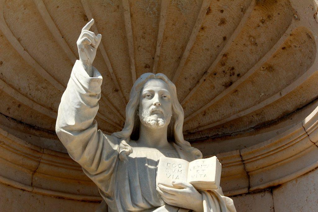 """Wie kommt man in den Himmel? Jesus zeigt mit der rechten Hand nach oben, in der linken hält er die Bibel mit dem Vers: """"Ego sum via et veritas et vita"""" = """"Ich bin der Weg und die Wahrheit"""""""
