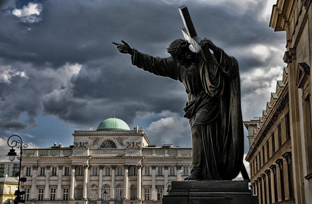 Christus-Statue vor der Kirche Ste. Croix in Warschau mit Dornenkrone auf dem Kopf und Kreuz auf der Schulter und ausgestrecktem Arm unter schwarzgrau bewölktem Himmel
