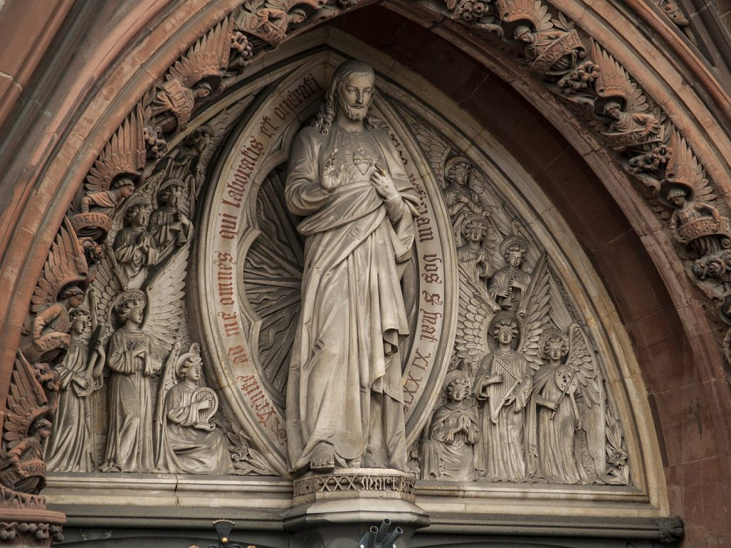 Erquicken durch Sanfmut und Demut: Jesusstatue über einem Kirchenportal mit der lateinischen Umschrift um ihn herum aus Matthäus 11, 28